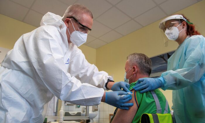 Harry Hoffmann (L), a Volkswagen company doctor, and nurse Nicolle Sprotte (R), vaccinate Steffen Martin, an employee at the Volkswagen Saxony plant, with the AstraZeneca vaccination in Zwickau, Germany on March 30, 2021. (Hendrik Schmidt/dpa via AP)