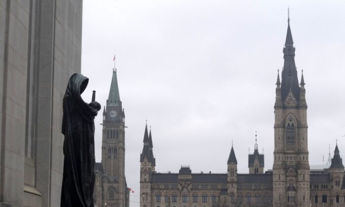 The justice statue at the Supreme Court of Canada, with the Parliament Buildings in the background, in Ottawa on March 25, 2021. (The Canadian Press/Adrian Wyld)