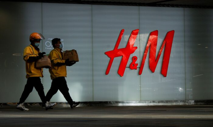 People walk past an H&M store in a shopping area in Beijing, China on March 28, 2021. (Thomas Peter/Reuters)