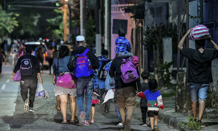 Migrants begin walking in a caravan on their way to the United States, in San Pedro Sula, Honduras, on March 30, 2021. (Wendell Escoto/AFP via Getty Images)