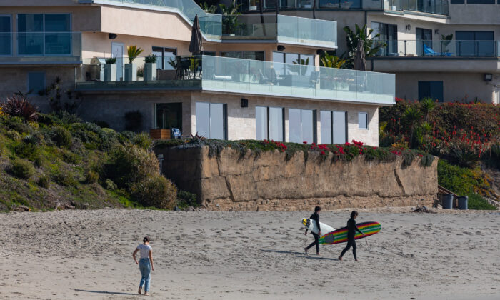 Surfers walk past a seawall built in front of a home at Victoria Beach, in the city of Laguna Beach, Calif., on Jan. 8, 2021. (John Fredricks/The Epoch Times)