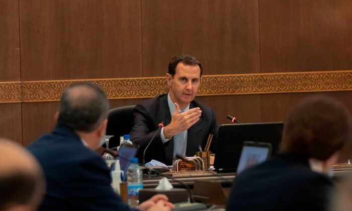 Syrian President Bashar Assad (C) heads a cabinet meeting, in Damascus, Syria, on March 30, 2021. (Syrian Presidency Facebook page via AP)