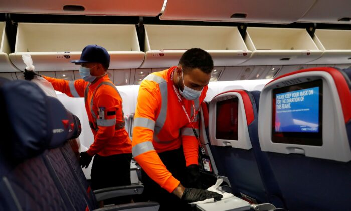 Delta Air Lines pre-flight cleaning crew members work on an aircraft at JFK International Airport, N.Y., on Aug. 6, 2020. (Shannon Stapleton/Reuters)