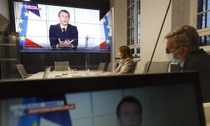 Local prefect Josiane Chevalier, second right, and her aide watch French President Emmanuel Macron addressing the nation, in the local government building in Strasbourg, eastern France, on March 31, 2021. (Jean-Francois Badias/AP Photo)