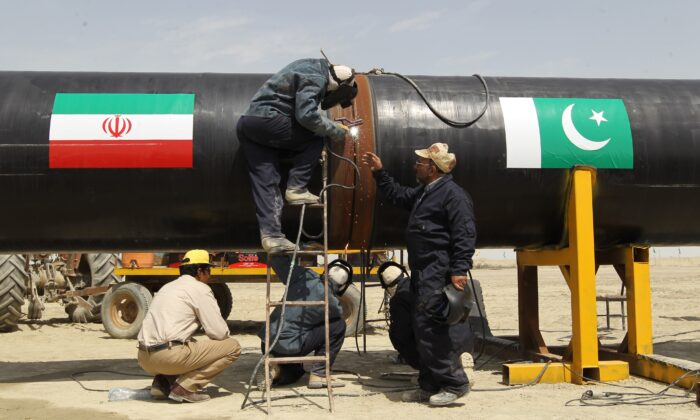 File image of workers working on a section of the Pakistan-Iran pipeline (with flags of both countries etched on it) in the Iranian border city of Chah Bahar while it was under construction in2013. (Atta Kenare/AFP via Getty Images)