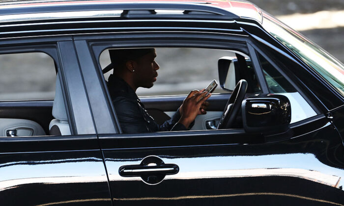 A driver in New York City uses a phone while behind the wheel of a car in this file photo.  (Spencer Platt/Getty Images)