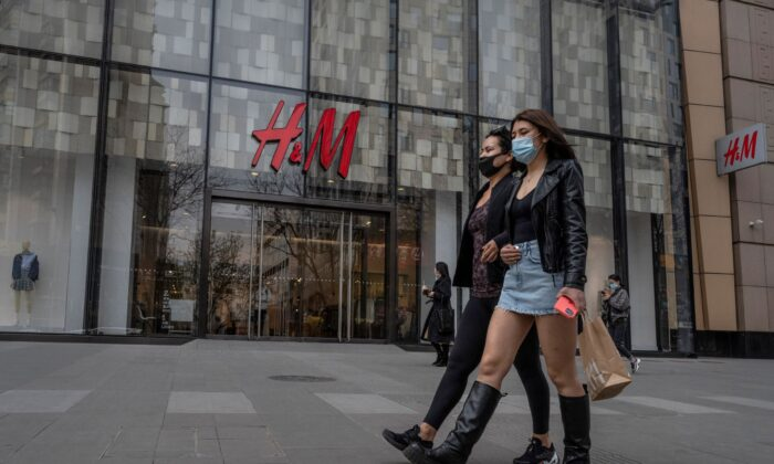 Women walk by an H&M clothing store in Beijing, China, on March 30, 2021. (Kevin Frayer/Getty Images)