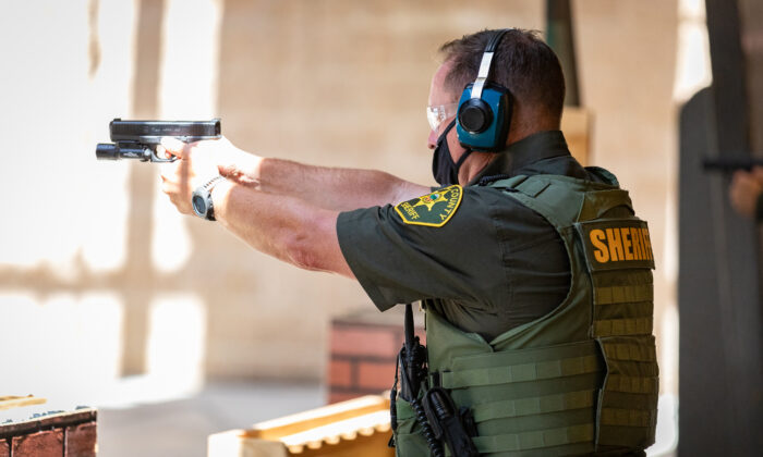 A deputy fires his weapon downrange at the Orange County Sheriff's Department  shooting range in Orange, Calif., on March 30, 2021. (John Fredricks/The Epoch Times)