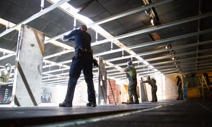 Police officers fire weapons downrange at the Orange County Sheriff's Department shooting range in Orange, Calif., on March 30, 2021. (John Fredricks/The Epoch Times)