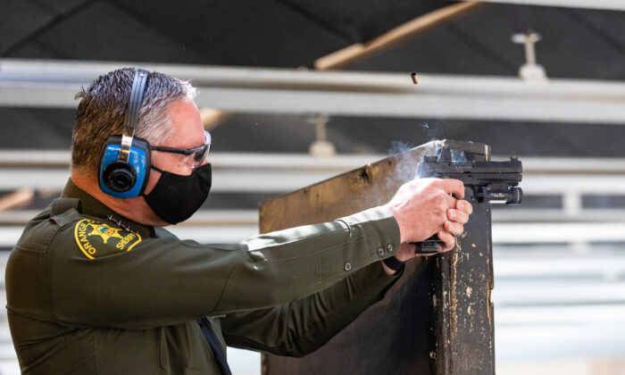 Orange County Sheriff Don Barnes fires his weapon at the Orange County Sheriff's Department shooting range in Orange, Calif., on March 30, 2021. (John Fredricks/The Epoch Times)