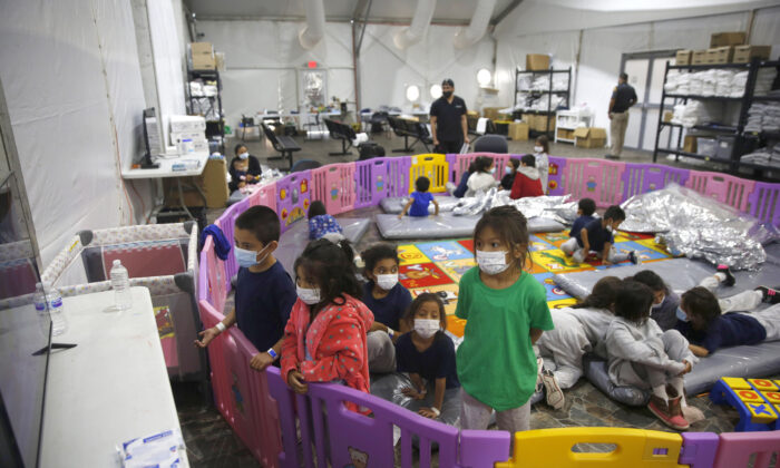 Young unaccompanied illegal immigrants, from ages 3 to 9, watch television inside a playpen at the U.S. Customs and Border Protection facility, the main detention center for unaccompanied children in the Rio Grande Valley, in Donna, Texas, on March 30, 2021. (Dario Lopez-Mills/Pool/AP Photo)