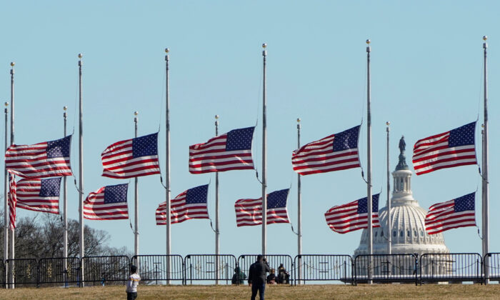 People walk past flags flying at half at the Washington Monument in memory of 500,000 deaths due to coronavirus disease (COVID-19) in Washington, on Feb. 24, 2021. (Joshua Roberts/Reuters)