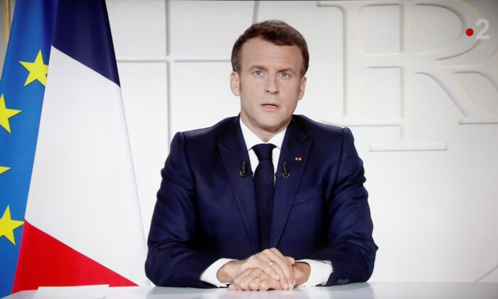 French President Emmanuel Macron is seen on a screen as he addresses the nation about the state of the CCP virus outbreak as a fast-spreading third wave of COVID-19 infections threatens to over-run hospitals in France, on March 31, 2021. (Stephane Mahe/Reuters)