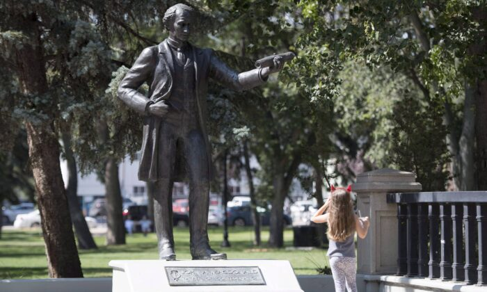 A little girl stops to look at a statue of John A. Macdonald in Victoria Park in Regina, Canada, on Aug. 22, 2018. (Jonathan Hayward/The Canadian Press)
