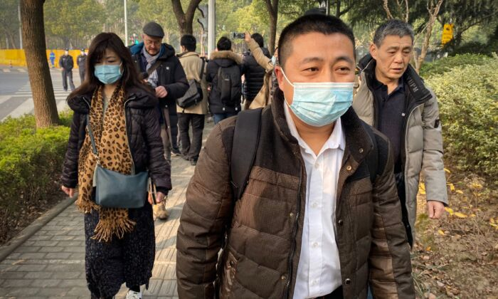 Lawyer Ren Quanniu (C), representing Chinese citizen journalist Zhang Zhan who reported on the virus outbreak, arrives at the Shanghai Pudong New District People's Court where Zhang is set for trial in Shanghai on Dec. 28, 2020. (Leo Ramirez/AFP via Getty Images)