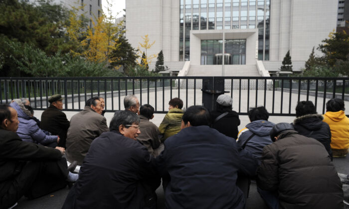 A group of elderly retirees from the Prison department in northeast China's Liaoning province, stage a sit-down protest outside the Chinese Ministry of Justice over their unpaid pensions  in Beijing, China on Nov. 8, 2011.                  (Goh Chai Hin/AFP via Getty Images)