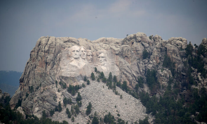 The busts of presidents George Washington, Thomas Jefferson, Theodore Roosevelt and Abraham Lincoln tower over the Black Hills at Mount Rushmore National Monument near Keystone, S.D., on July 2, 2020. (Scott Olson/Getty Images)