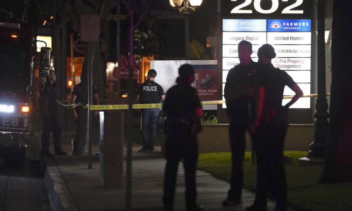Police officers stand outside a business building where a shooting occurred in Orange, Calif., on March 31, 2021. (AP Photo/Jae C. Hong)