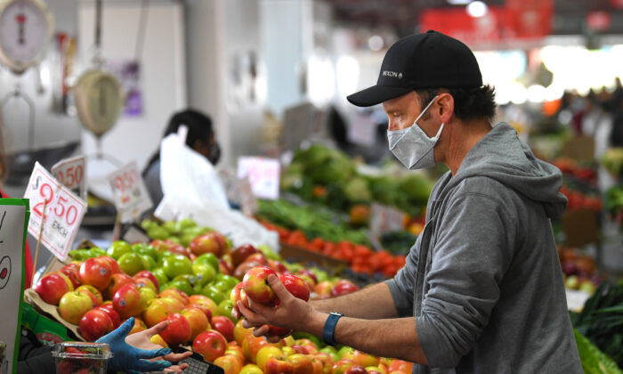 People are seen shopping for fruit and vegetables at the Queen Victoria Market in Melbourne, Sunday, Oct. 18, 2020. (AAP Image/James Ross)