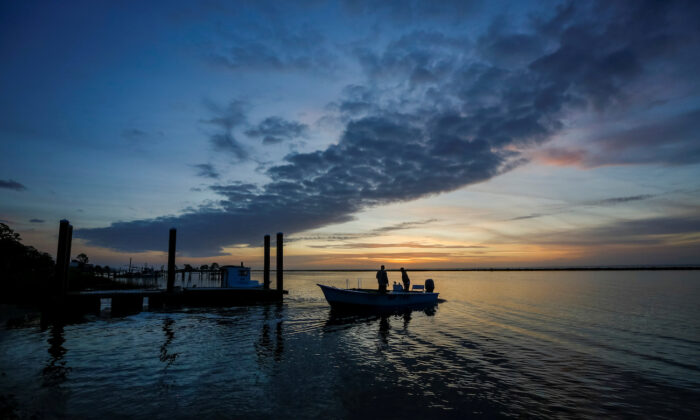 A boat leaves before dawn for a day of work harvesting oysters from Apalachicola Bay, Feb. 11, 2020. (Colin Hackley/Reuters)