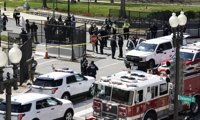 Police and fire officials stand near a car that crashed into a barrier on Capitol Hill in Washington, on April 2, 2021. (J. Scott Applewhite/AP Photo)