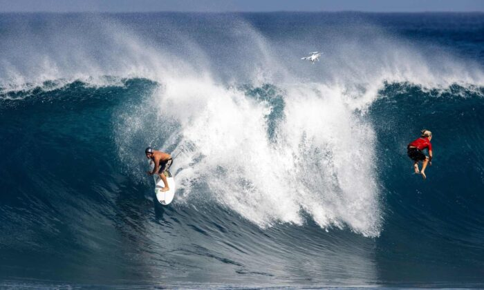 A surfer rides a wave as another one gets wiped out at Pipeline on the north shore of Oahu, Hawaii, on Feb. 14, 2021. (Brian Bielmann/AFP via Getty Images)