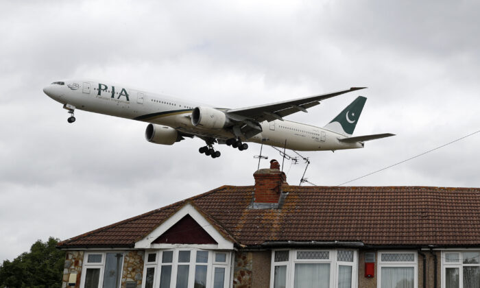 A Pakistan International Airlines Boeing 777 comes in over houses, to land at Heathrow airport in west London on June 8, 2020. (Adrian Dennis/AFP via Getty Images)