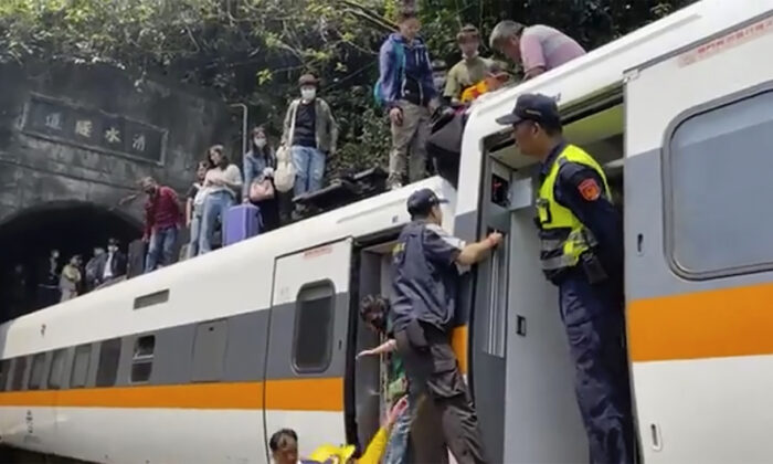 In this image made from a video released by hsnews.com.tw, passengers are helped to climb out of a derailed train in Hualien County in eastern Taiwan, on April 2, 2021. (hsnews.com.tw via AP)