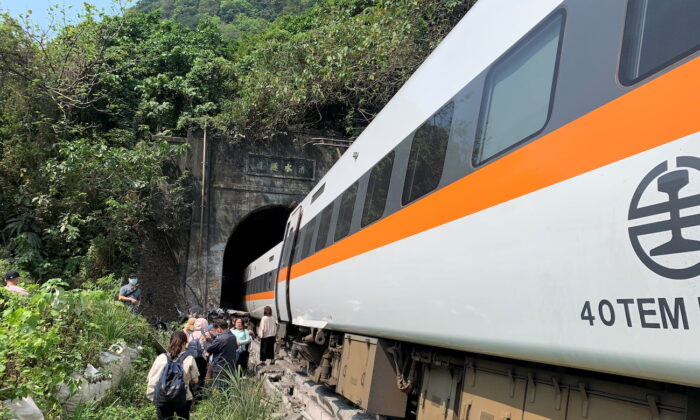 People walk next to a train which derailed in a tunnel north of Hualien, Taiwan, on April 2, 2021. (Taiwan's National Fire Agency/Handout via Reuters)
