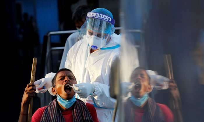 A healthcare worker collects a CCP virus test swab sample from a man, at a temporary shelter for homeless people in New Delhi, India, on March 31, 2021. (Adnan Abidi/Reuters)