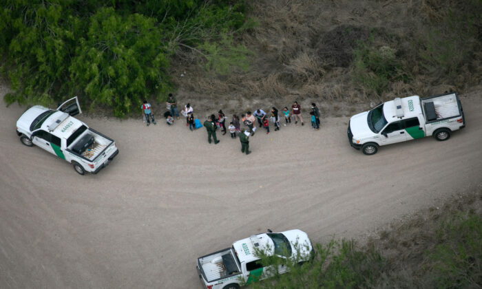 U.S. Border Patrol agents take illegal immigrants into custody, as seen from a Texas Department of Public Safety helicopter, near the U.S.-Mexico Border in McAllen, Texas, on March 23, 2021. (John Moore/Getty Images)