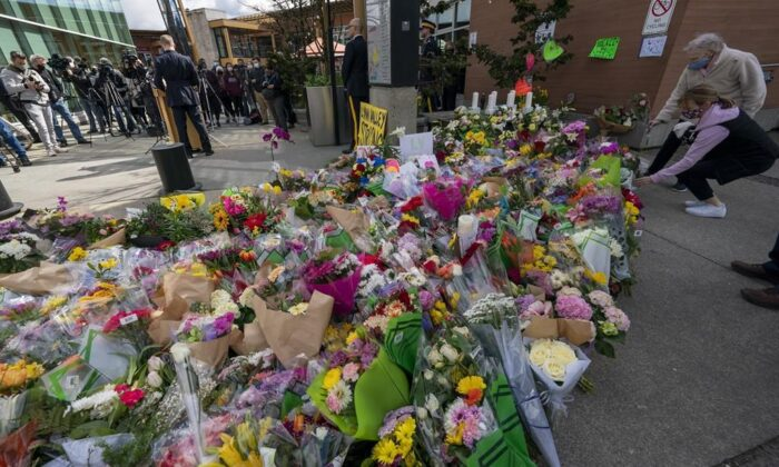 A lady places flowers at a makeshift memorial as the RCMP give a news conference outside of the Lynn Valley Library in Lynn Valley in North Vancouver, B.C., on March 29, 2021. (The Canadian Press/Jonathan Hayward)