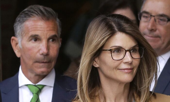 Actress Lori Loughlin, front, and her husband, clothing designer Mossimo Giannulli, left, depart federal court in Boston after facing charges in a nationwide college admissions bribery scandal on April 3, 2019. (Steven Senne/AP)