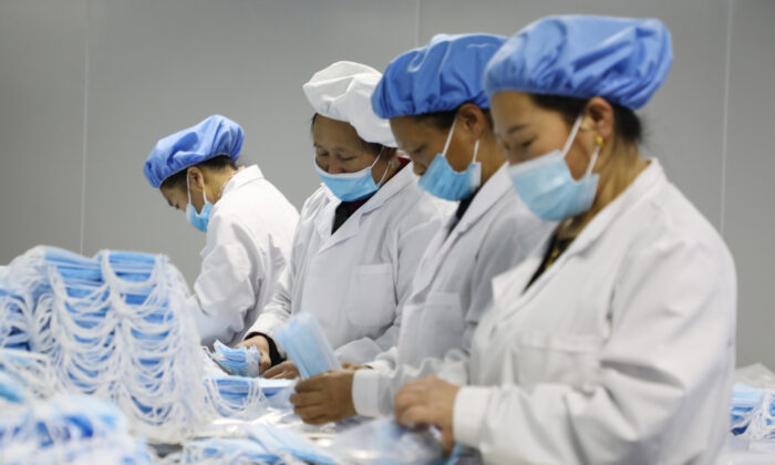 Workers making medical masks at a factory in Jishou, Hunan Province, China, on Jan. 28, 2021. (STR/AFP via Getty Images)