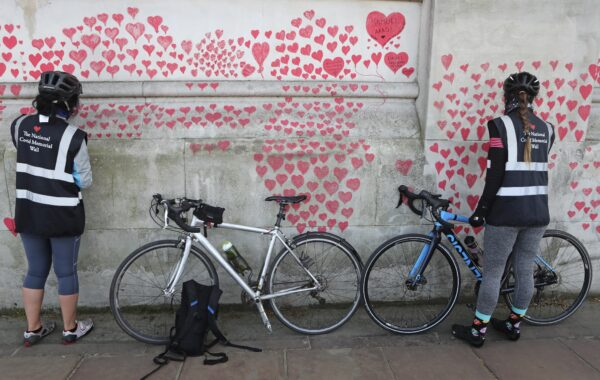 Women draw hearts on the 'The National COVID Memorial Wall'
