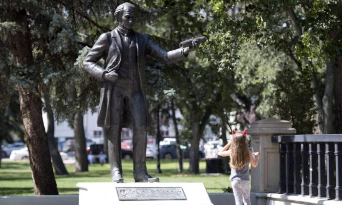 A little girl stops to look at a statue of John A. Macdonald in Victoria Park in Regina on Aug. 22, 2018. (Jonathan Hayward/The Canadian Press)