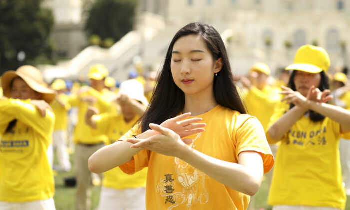 Falun Gong practitioners perform slow-moving exercises at a rally commemorating the 20th anniversary of the persecution of Falun Gong in China, on the West Lawn of Capitol Hill on July 18, 2019. (Samira Bouaou/The Epoch Times)