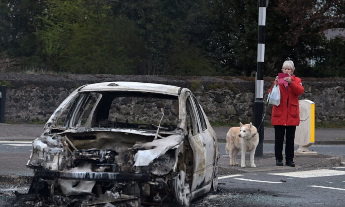 A woman takes a photograph with her smart phone of a burnt out car at the Cloughfern roundabout junction following overnight Loyalist violence on April 4, 2021 in Belfast, Northern Ireland. (Charles McQuillan/Getty Images)