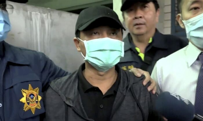 In this image taken from video, Lee Yi-hsiang, the driver of the truck that caused the train accident on Saturday, offers a public apology as he is led by police, in Hualien, Taiwan, on April 4, 2021. (EBC via AP)