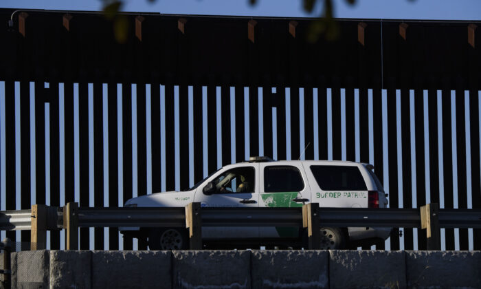 A U.S. Border Patrol agent sits in a vehicle along a border wall near the U.S. Customs and Border Protection San Ysidro Port of Entry at the U.S.-Mexico border in San Diego, Calif., on Feb. 19, 2021. (Patrick T. Fallon/AFP via Getty Images)