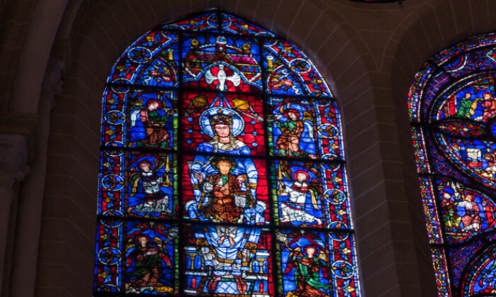 """A detail of one of the oldest stained glass windows in the cathedral is the """"Notre-Dame de la Belle-Verrière,"""" or """"The Blue Virgin"""" window. The upper window dates from around 1180 and shows the Virgin Mary sitting on a throne as she holds Christ on her lap. His hand gesture signifies a blessing. (Cynthia Liang/Shutterstock)"""