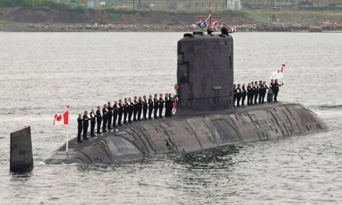 Sailors line up on Canadian submarine HMCS Corner Brook to salute Queen Elizabeth II during an international fleet review on June 29, 2010, in Halifax. An internal Defence Department report that says an errant test on one of Canada's four beleaguered submarines last year caused permanent damage to the vessel that will continue to pose a risk over the long term. (Paul Chiasson/The Canadian Press)