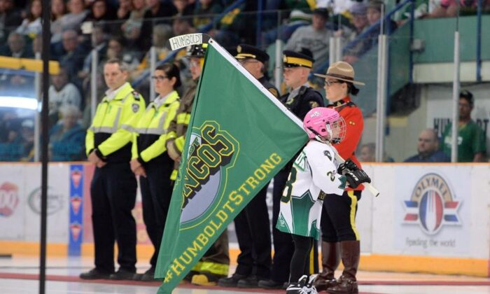 A girl skates with a Humboldt Broncos flag as she skates by first responders during a tribute to the team after their SJHL game against the Nipawin Hawks in Humboldt, Sask., on Sept. 12, 2018. The City of Humboldt has announced an ambitious plan to permanently commemorate the deadly Broncos bus crash. (Jonathan Hayward / The Canadian Press)