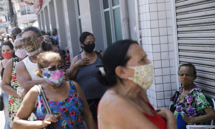 People wait in line to receive a dose of the Sinovac's CoronaVac vaccine during a vaccination day for 65-year-old and older citizens in Duque de Caxias near Rio de Janeiro, Brazil, on March 29, 2021. (Ricardo Moraes/Reuters)