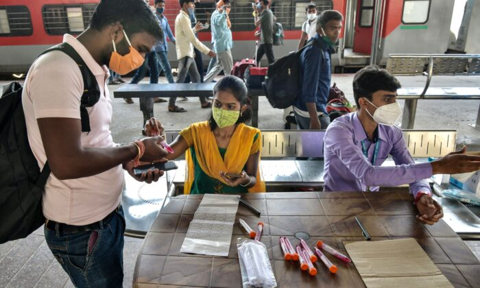 Health workers register passengers to collect samples for virus test at the Yesvantpur railway station in Bangalore, India, on April 5, 2021. (Manjunath Kiran/AFP via Getty Images)