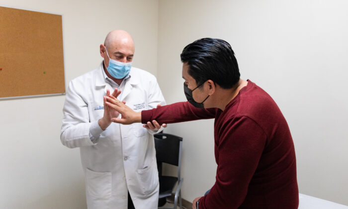 Patient Israel Zuniga (R) receives treatment from Dr. David Millet at the Lestonnac Free Clinic in Orange, Calif., on March 19, 2021. (John Fredricks/The Epoch Times)
