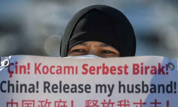 A Uyghur holds a sign asking the Chinese regime to release her husband at a parade near the Chinese consulate in Istanbul, Turkey on Feb. 22, 2021. (Ozan Kose/AFP via Getty Images)
