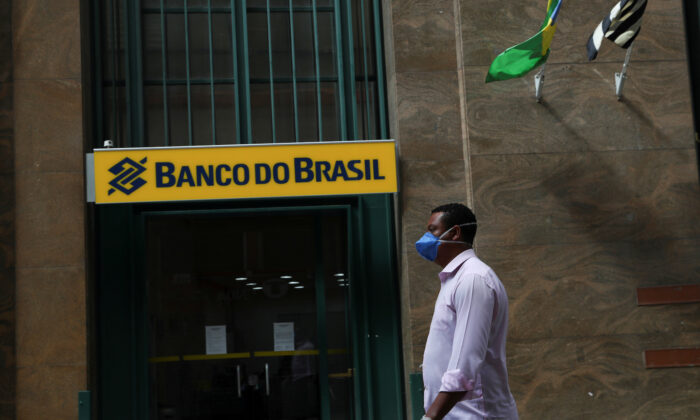 A man wearing a protective mask and gloves walks in front of Banco do Brasil (Bank of Brazil) during the COVID-19 outbreak in Sao Paulo, Brazil, on March 24, 2020. (Amanda Perobelli/File Photo via Reuters)