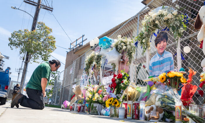 A man prays and mourns in Orange, Calif. April 5 next to a memorial set up in front of a business building where four people were killed on March 31, 2021. (John Fredricks/The Epoch Times)