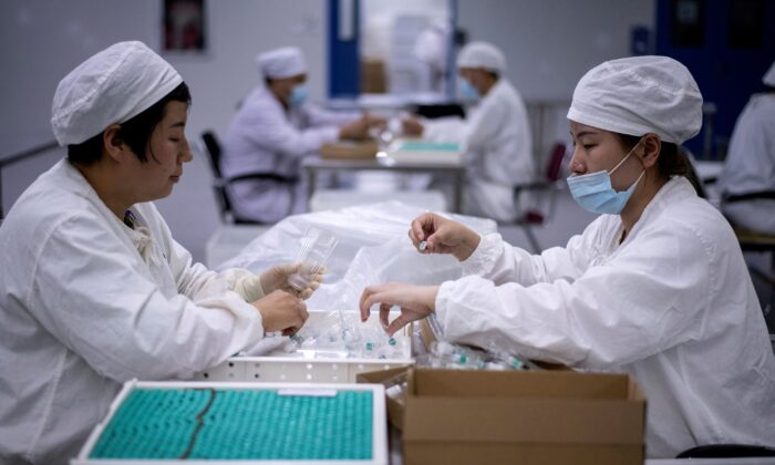 Workers package rabies vaccine at a lab where researchers are trying to develop a vaccine for the COVID-19 coronavirus, in Shenyang, in China's northeast Liaoning province, on June 9, 2020. (Noel Celis/AFP via Getty Images)